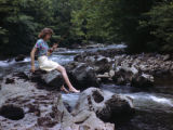 Young girl fishing along a stream in the Great Smoky Mountain National park, circa 1940s