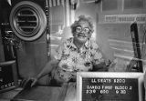 Movie theater employee sitting in the box office of the Rialto Theatre, 1985
