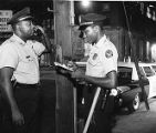Two Atlanta police officers phone in to the station on a night watch, 1965
