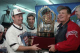 Atlanta Braves manager Bobby Cox holding the World Series trophy with Ted Turner and team...