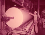 Coosa River Newsprint Co. factory worker rolling a large supply of finished newsprint, 1950