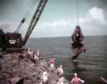 Salvage crew pulls one of two shipwrecks out of the sea, 1957