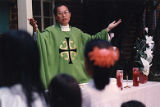 Father Francis Phyong at the Vietnamese American Community leads an evening Catholic service, 1994