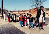 Woman leading children to their pre-school, after police patrol in public housing stepped up,...