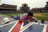 Worker painting Turner Field above the visiting team's dugout, 1997