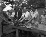Governor Ellis Arnall prepping food with his supporters during a campaign rally, 1944
