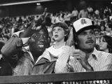 Braves owner Ted Turner watches a home game with retired baseball legend Hank Aaron, 1977