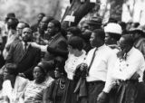 Onlookers point out the casket of Martin Luther King Jr. during the funeral procession through...