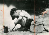 Young boy with fishing pole, crouched by edge of lake, Atlanta, Georgia, July 1963.