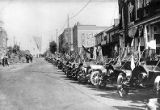 Vehicles from the Good Road Tour parked along the storefronts of Lexington, 1910