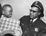 Police officer Ernest H. Lyons working with a child from the community, 1968
