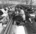 Textile worker inspects one of many rows of machines at a textile plant, 1971
