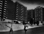 Two boys do cartwheels outside Cosby Spear Memorial Towers (335 North Avenue, NE), public housing...