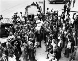 Crowd cheers the end of prohibition on the sale of liquor, as crates of liquor are brought into a...