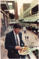 Man eating tacos on upper floor of Underground Atlanta, Atlanta, Georgia, 1980s?