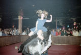 Patron, Kristin Pettit, riding a mechanical bull at Mama's Country Showcase, Belvedere Park,...