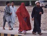 Muslim woman in full burqa walking with three men from her family on a city street, South Asia or...