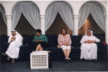 Two Arab couples sitting on long sofa bank, Middle East (?), photograph by Jean Shifrin, 1992.