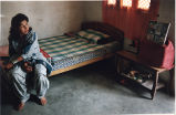 Muslim woman at home, sitting on a bed, South Asia or Middle East, photograph by Jean Shifrin,...