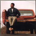 Man sitting on the edge of a rugged truck bed, Georgia, 1980s?