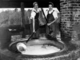 Two women wearing overalls, cooking kettle of cane syrup, Richland, Georgia, before 1939.