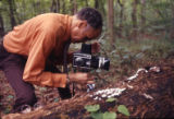 Scientist photographing fungus on a fallen tree for the Fernbank Science Center, Atlanta, Georgia,...