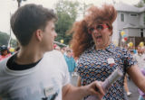 Nurse Holly from Bulldog's gets the attention of a crowd member in an AIDS walk, by go-go dancing,...