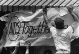 AIDS banner goes up at the gay pride rally site, Atlanta, Georgia, June 25, 1983.