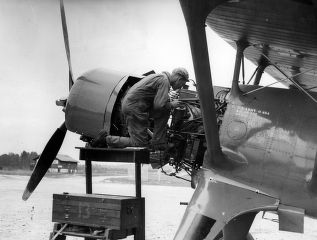 "Mechanic inspecting the engine of an ""observation plane,"" Fort Benning, Georgia, 1937?"