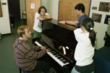 "Students gathered around a piano, rehearsing for ""Peep Show,"" a live performance put on..."