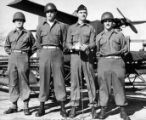 Four soldiers standing in front of small pilotless, remote-control plane at For Benning, Georgia....