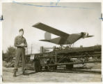 Captain Richard M. Horton standing, holding the remote-control in front of the OQ Robot Plane,...