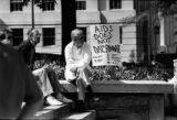 "Demonstrator at AIDS rally and vigil, sign reads ""AIDS does not discriminate. Fight AIDS, not..."