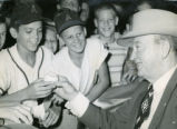 Ty Cobb, baseball great, autographs a ball for young fans, 1950s