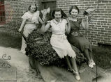 Martha Louise Johnson, Maranelle Hatcher, and Marion Majors pose with a wheelbarrow of tobacco,...