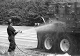 Fire fighter Jeff Hogan hosing down a truck fire at I-285 and Roswell Road, Atlanta, Georgia, June...