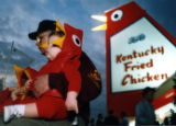 "Infant Josiah Mize wearing a ""Big Chicken"" costume with his grandfather, Donnie Edwards,..."