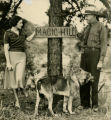 "Woman and park ranger, with German shepherd dog, look at sign for ""Magic Hill,"" near..."