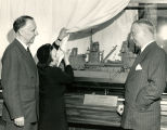 Margaret Mitchell unveils a model of ship, U.S.S. Atlanta, with Atlanta Mayor Hartsfield (right)...