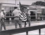 Police officers raising the flag at the new Lyons, Georgia, municipal building, June 1973.