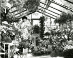 Woman watering plants in the Atlanta Botanical Garden's new gift shop greenhouse