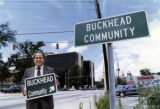 Former Mayor Sam Massell holds a replica Buckhead community sign next to the real street sign, 1991
