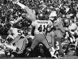 Herschel Walker leaps over the defensive line in an attempt to gain yardage, 1980