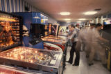 Arcade of pinball machines and video games being played, 1980