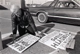 KKK supporter gathers hand painted signs for a demonstration, 1988
