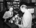 Store clerk and customer interact within a pharmacy, circa 1940s