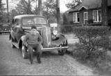 David Lennox Jr. sitting on the bumper of his 1937 Ford, Atlanta, Georgia, circa late 1930s or...