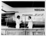 Apprentice and mechanic preparing to open engine cowling of JT8D engine on a Boeing 727 aircraft,...