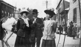 Man and two women stroll down street, C. J. French collection