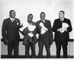 Four African-American union members pose with back pay checks